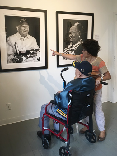 Filipino WW2 veteran and Purple Heart recipient Patricio Ganio looking at his portrait at The Yellow House Gallery