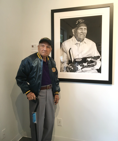 Filipino WW2 veteran and Purple Heart recipient Patricio Ganio standing next to his portrait